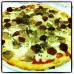 Pizza de secreto de cerdo ibérico con queso brie y cebollas caramelizadas